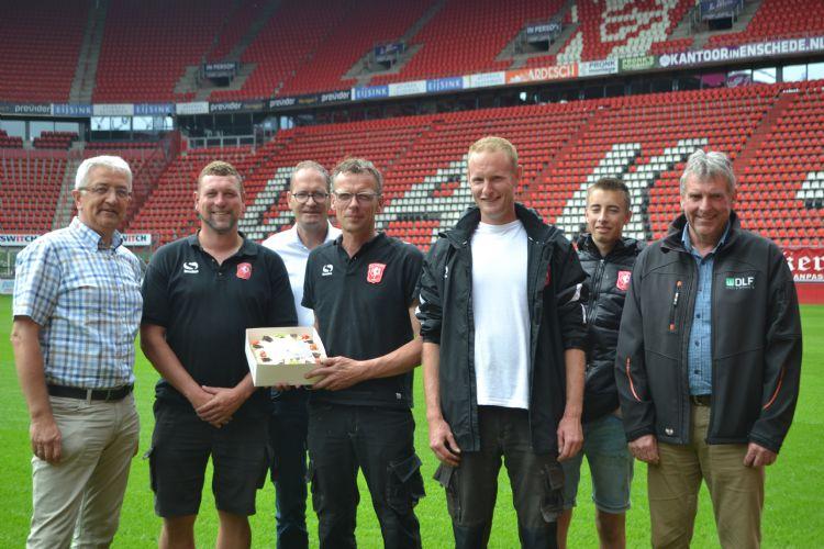Mark Timmerman (Prograss), Harry van het Hof (Compo Expert) en Henk Roelofsen (DLF) feliciteren de fieldmanagers van FC Twente met hun VVCS-titel.