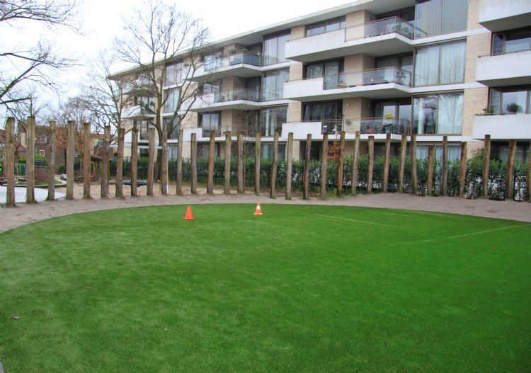 Het veld ligt naast een aantal appartementen.