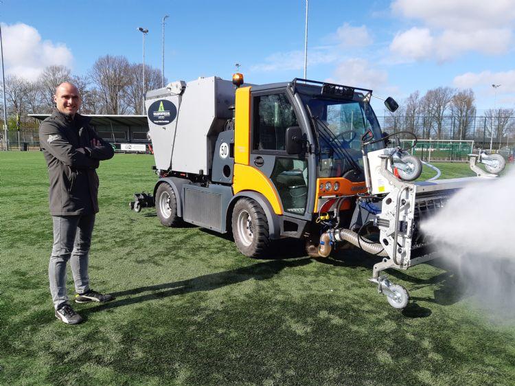 Martijn Bakker (Veiligsportveld) met de reinigingsmachine op het veld bij vv Schoten