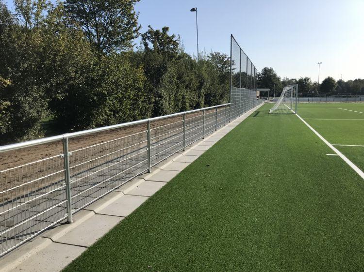 Kunstgrasveld in Pesse met betonplaten met opstaande rand. Deze rand zorgt ervoor dat de infill op het veld blijft liggen.