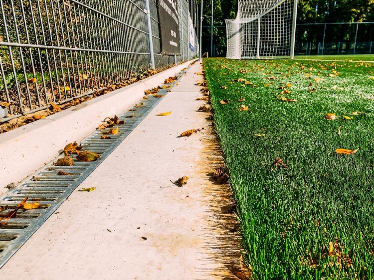 De betonplaat ligt langs één lange en één korte zijde, die grenzen aan een groenstrook.
